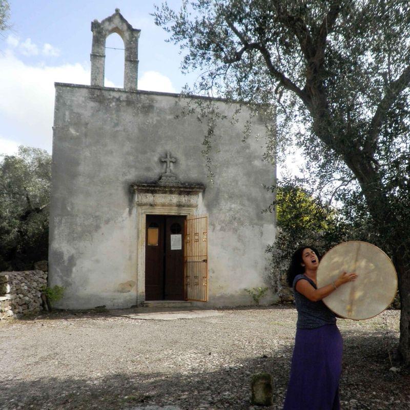 suonatrice di pizzica di fronte alla cappella di san vito a calimera